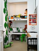 Fitted shelves of cushions and toys in niche next to floor-length, leaf-patterned curtains in child's bedroom