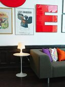 Tulip side table and dark grey couch with scatter cushions below decorative letters and artworks on wall above wainscoting