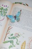 Paper butterfly on open, antiquarian plant book