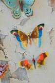 Colourful butterfly ornaments on wooden board with peeling paint