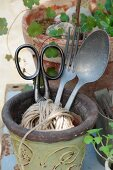 Old scissors, aluminium cutlery and packing string in vintage planter