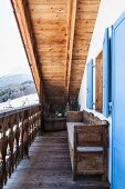 Wooden balcony of restored Swiss chalet with sky-blue shutters and view of snowy mountain landscape