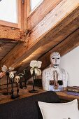 Collection of artistic papier mâché flowers and modern bust on L-shaped shelf under sloping ceiling with dormer window