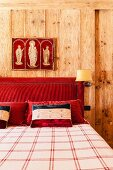 Religious triptych above red upholstered headboard of double bed; walls panelled in solid, plain wood