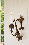 Lit candle in metal, vintage-style candle sconce with floral elements on pale wooden wall