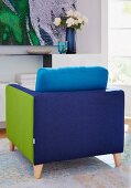 A comfortable patchwork armchair in blue and green on a rug