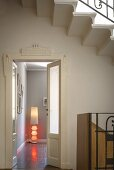 White Art Deco door frame; modern standard lamp with red light elements in corner