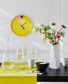 A home-made wall clock – an old tray painted and fitted with a clock mechanism on a whitewashed brick wall with a glass carafe and wine glasses on a yellow table runner next to a bunch of flowers in a white vase on a black table