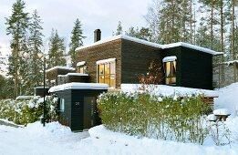 Modern, Scandinavian, flat-roofed house clad in dark wood in snowy winter landscape