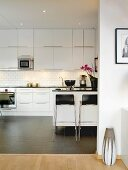 White, modern fitted kitchen with tiled floor, worksurface and bar stools in contrasting black