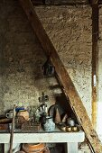 Antique kitchen pots on stone table in old, converted stable