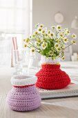 Home-made crocheted vases in purple and red with daisies