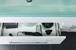 Detail of washstand with a glass top and a half open drawer with a view of a hairdryer and accessories