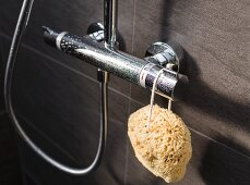 A natural sponge hanging on a shower tap mounted on brown, marbled wall tiles