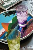 Coloured glasses of iced water on tray with picture of Sugarloaf Mountain in Rio de Janeiro, Brazil