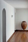 Amphora in metal frame against wall in empty room with arched doorway