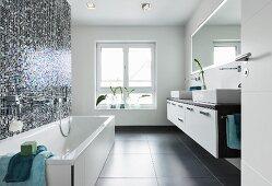 Blauweiss changierendes Fliesenmosaik über Badewanne; gegenüber ein Doppelwaschtisch mit Aufsatzbecken und wandbündigem Lichtspiegel