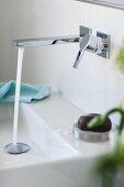 Starker Wasserstrahl aus Wandarmatur in kubisch geformtes Waschbecken