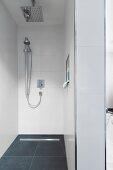 Kopf- und Handbrause in begehbarer moderner Dusche mit Ablaufrinne