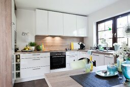 A white modern fitted kitchen with shiny white fronts and a wooden look dining table in the foreground