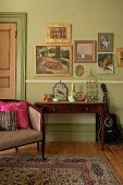 Small gallery of pictures on pastel green wall above ornaments and bird cage on writing desk; art nouveau armchair with various scatter cushions