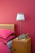 Bedside cabinet with lamp against raspberry wall next to Art Nouveau bed with cane headboard and pink bed linen