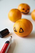 Drawing spooky Jack-o'-lantern faces on tangerines for Halloween