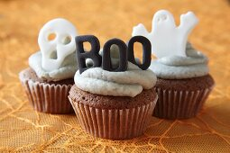 Halloween cupcakes decorated with buttercream icing and spooky cake toppers