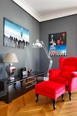 Bright red wing-back chair with footstool and reflections in glossy sideboard below surrealist painting on grey-painted wall