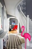 Pink flamingo sculpture at foot of staircase in elegant foyer with view into living room