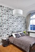 Double bed with grey, velvet throw against wallpaper with pattern of women's faces