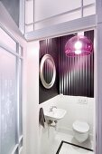 View through open door into elegant toilet with glossy, striped wallpaper and extravagant, purple, plexiglas lampshade