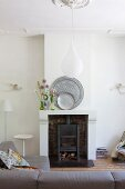 Pewter plates and wild flowers on mantelpiece; teardrop-shaped pendant lamp above sofa