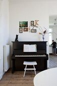 Pictures, letter K and framed butterflies on wall above piano with cat ornament and flowers on top