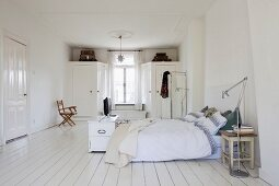 Large bedroom with Scandinavian, vintage ambiance; old kitchen stool used as bedside table and window flanked by fitted wardrobes