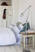 Old kitchen stool used as bedside table, modern standard lamp, bed linen with patterned trim and retro screen