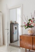 Bulbous vase of flowers on retro sideboard next to open door showing old wooden cupboard in ensuite bathroom