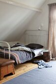 Tree stump table on castors and clothing on floor next to metal-framed bed with grey cover; old vaulting horse at foot of bed