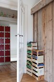 Two stacks of fruit crates for storing toys between board wall and open interior door with view into hallway