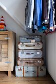 Laundry stored in stacked vintage suitcases in bedroom below jackets and shirts hanging up next to rustic sideboard