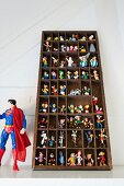 Collection of colourful comic-book figurines in display case next to larger Superman action figure