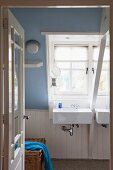 Sinks below dormer window in bathroom with white-painted wood and sloping ceiling painted lavender blue