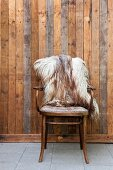 Antique bentwood chairs with sheepskin blanket against board wall