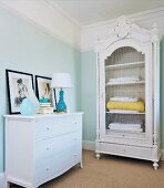 White chest of drawers and antique, white-painted, carved cupboard with wire door panel in corner of bedroom