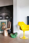 Yellow shell chair by Eero Saarinen and chair shaped like hand in front of picture of Buddha