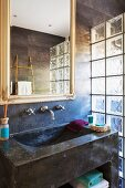Concrete sink and mirror on dark marbled wall with glass brick partition to one side