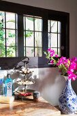 Delft vase of bougainvillea in front of Spanish, lattice windows, natural finds on cake stand on wooden surface