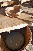 Rough wooden bowl on rustic table and wicker armchair in sunlight