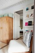 Chair with patterned scatter cushion in front of bookcase and simple wooden cupboard in Mediterranean bedroom