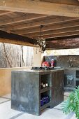 Outdoor kitchen with wooden ceiling, marbled concrete counters and glass lamp above hob on free-standing block
